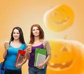 education, holidays, friendship, drinks and people concept - smiling student girls with books and paper coffe cups over halloween pumpkins background