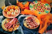 some plates with Halloween food, such as candies, scary fingers or mandarines as pumpkins, with different scary ornaments as spiders, cobwebs or a tombstone