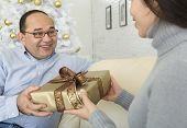 Hispanic woman giving gift to man
