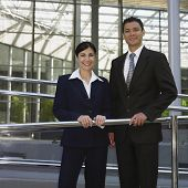 Businessman and businesswoman leaning on railing