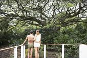 Multi-ethnic couple leaning on railing