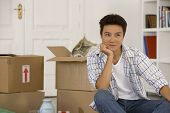 Asian man next to unpack moving boxes