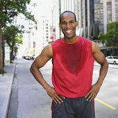 African man wearing sweaty shirt in city