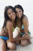 South American women hugging at beach