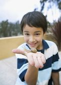 Hispanic boy holding snail