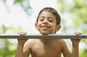 Hispanic boy leaning chin on bar