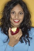 stock photo of indian apple  - Portrait of Middle Eastern woman eating apple - JPG