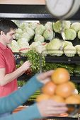 Man looking at vegetables in grocery store