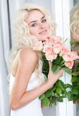 Stunning young blond woman with a bouquet of roses given to her by a sweetheart or loved one for Valentines, an anniversary or birthday smiling at the camera
