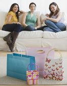 Three young women looking at gift bags