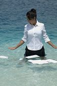 Hispanic businesswoman with papers in water