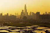Air pollution scenic in countryside with building, rice field and yellow smoke in hong kong city at sunset