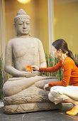 Asian woman placing flower on Buddha statue