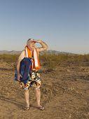 Senior Mixed Race man wearing bathing suit in desert