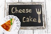 Cheese cake on paper napkin on blackboard on wooden background
