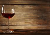 Goblet of red wine on wooden table on wooden wall background