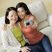 Asian mother and adult daughter taking own photograph