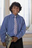 Mixed Race boy holding school books