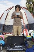 Hispanic boy surrounded by camping supplies