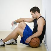 Hispanic man in athletic gear with basketball