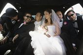 Hispanic newlyweds and family in limousine