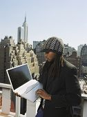 African man looking at laptop in urban scene