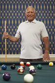 Senior Mixed Race man holding pool cue