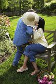 Hispanic couple hiding behind straw hat