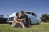 Hispanic couple in front of low rider car