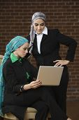 Middle Eastern businesswomen looking at laptop