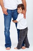 Small child holding his father leg - the safety provided by a parent