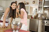 Hispanic teenaged girls telling secret