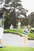 Asian couple playing golf
