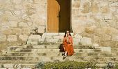 Hispanic woman sitting on stone steps