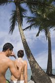 Asian man applying sunscreen to girlfriend