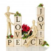 Rustic alphabet blocks arranged to say LOVE, JOY, PEACE.  It also includes two wooden mannequins and is adorned with Christmas holly and poinsettias.  On a white background.