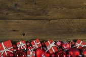 Christmas frame, card or advertising board with red presents on wooden old background.