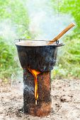 Cooking Goulash soup in cauldron on Finnish (Swedish) log stove