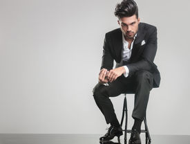 image of stool  - Elegant young man in tuxedo sitting on a stool while holding his finger - JPG