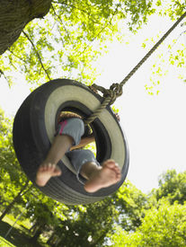 picture of tire swing  - Barefoot girl on tire swing - JPG
