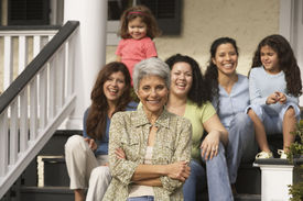 picture of grandmother  - Hispanic grandmother with female family members in the background - JPG