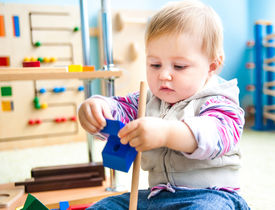 pic of playgroup  - cute little girl in the classroom early development plays with numerous  toys - JPG