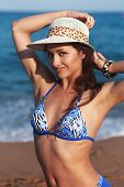 foto of armpit  - Beautiful bikini woman with epilation armpit on blue sea background looking with happy smile - JPG