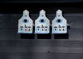 Three Bird Houses On A Wooden Wall