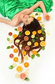 young woman lying on white background with oranges around her hair