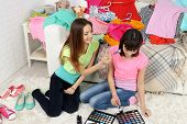 Two girls with clothes and decorative cosmetics at home