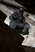 stock photo of extremist  - Armed man in black uniform standing on the steps in urban ruins - JPG