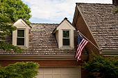 stock photo of gabled dormer window  - American Flag Hanging over Wood Shingles and Dormers - JPG