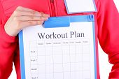 Sports trainer with personal workout plan close-up