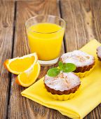pic of bakeshop  - Homemade Muffins Ready for Breakfast with orange slices and juice on a wooden background - JPG